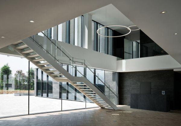 La scala di acciaio e vetro che conduce al piano primo della palazzina uffici di Corman