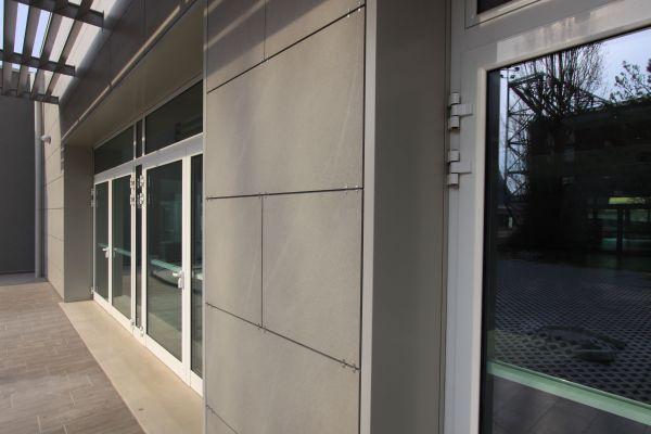 Il sistema è costituito da un pannello in poliuretano espanso rigido autoestinguente rivestito da una lamina in alluminio goffrato e da un correntino asolato in acciaio protetto, integrato nel pannello in fase produttiva, che forma un'orditura metallica portante, supporta il fissaggio del rivestimento esterno e crea la camera di ventilazione fra la cortina esterna e l'isolante.     Isotec Parete tra i molti vantaggi si caratterizza per massima versatilità, in questo caso ha semplificato la posa del rivestimento in lastre 120x60 cm in gres porcellanato di Emilgroup, ancorato ai correnti metallici con morsetti in acciaio a vista, senza che ci siano stati problemi dovuti alla metodologia di posa delle lastre a giunti sfalsati.     Tutta la realizzazione è stata seguita con molta cura: gli imbotti delle aperture sono stati isolati con i pannelli Isotec Linea, complementari e perfettamente raccordati ai pannelli Isotec Parete utilizzati in facciata e rivestiti successivamente con elementi in alluminio preverniciato.